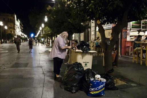 Una persona busca comida en un contenedor de basura en una calle de Sevilla.