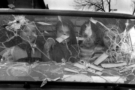 Cuatro niñas miran desde el interior de una furgoneta destrozada.