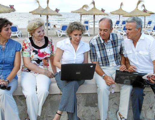 La alcaldesa Aina Calvo; la regidora de Medi Ambient, Begoña Sánchez; la presidenta de la asociación de hoteleros de Ciudad Jardí, María Fulana; y vecinos, probando el wi-fi en la playa.