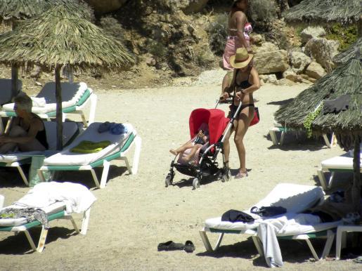 Toni Acosta junto a su hija a su llegada a la playa.