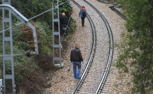Miembros de la Policía Científica buscan pruebas junto a la vía de tren en las inmediaciones del apeadero de La Argañosa, a las afueras de Oviedo, donde hallaron un niño de dos años muerto en el interior de una maleta.
