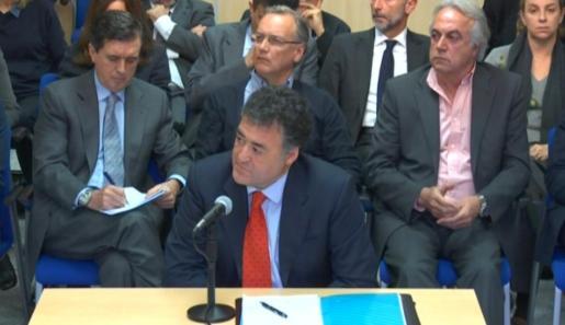 """Jaume Matas, en segundo plano a la izquierda, toma notas durante la declaración de """"Pepote"""" Ballester en el juicio del Caso Nóos."""