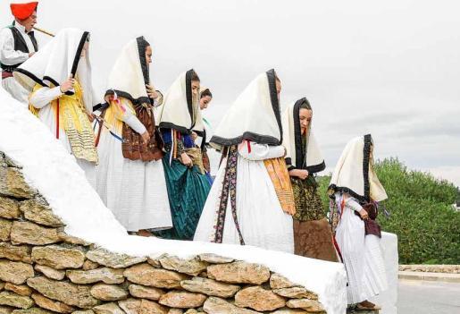 Unas jóvenes vestidas de payesas descienden del Puig de Missa. Foto: TONI ESCOBAR
