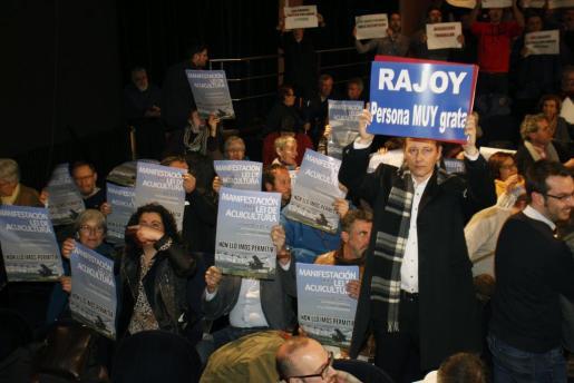 Muchos de los asistentes al pleno municipal de Pontevedra que ha nombrado al presidente del Gobierno en funciones Mariano Rajoy 'persona non grata' por ampliar la concesión, por sesenta años, a la celulosa Ence, que seguirá en la ría, muestran diversas pancartas reivindicativas.