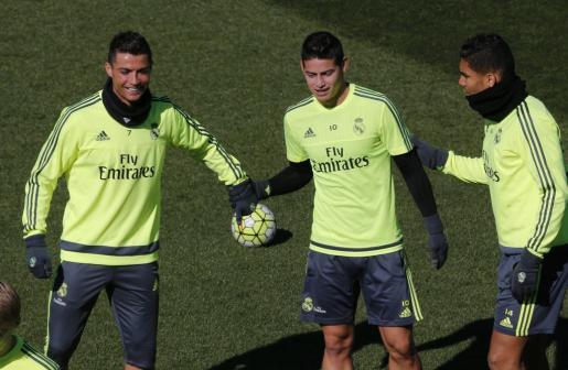 Los jugadores del Real Madrid Cristiano Ronaldo (i) James Rodríguez (c) y Casemiro (d), durante el entrenamiento realizado este martes en la Ciudad Deportiva de Valdebebas.