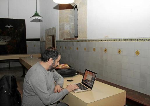 Pere Terrasa, en el antiguo refectorio de Santa Elisabet, con un gran cuadro de 'La última cena' al fondo, dispuesto a volcar en el ordenador los datos del medidor de temperatura.