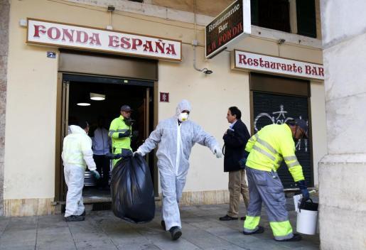 Trabajadores de Cort limpian uno de los locales que fueron precintados y que estaba situado en la Plaza Mayor de Palma.