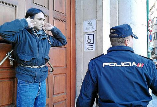 Un policía charla con Raúl Nicolás durante su acto de protesta.
