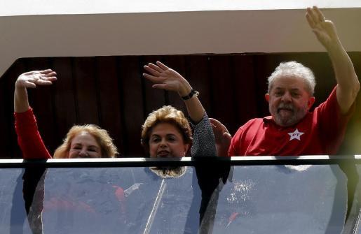 Lula da Silva con su esposa, y la presidenta Dilma Rousseff (en el centro), saludando desde la ventana de su casa durante la visita que ésta le hizo tras el interrogatorio del 'Caso Petrobras'.