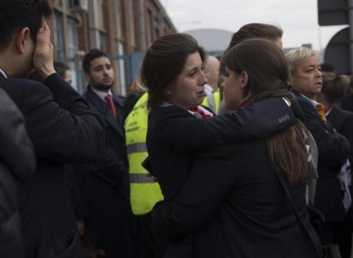 Varias trabajadoras del aeropuerto se abrazan mientras son evacuadas junto a los pasajeros de la zona aeroportuaria tras registrarse explosiones en el aeropuerto internacional de Zaventem.