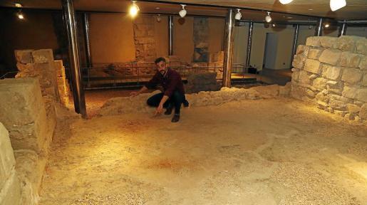 El arqueólogo Llorenç Vila señala la decoración en color rojo almagra del suelo del gran salón del palacio.