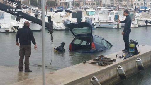 La grúa retira el vehículo caído al mar este viernes en el Portixol.