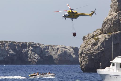 Uno de los helicóptero recoge agua para sofocar las llamas.