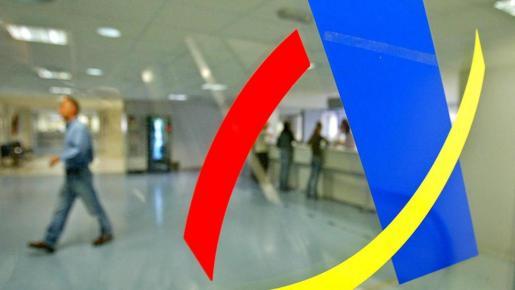 El logo de la Agencia Tributaria en el cristal de una oficina.