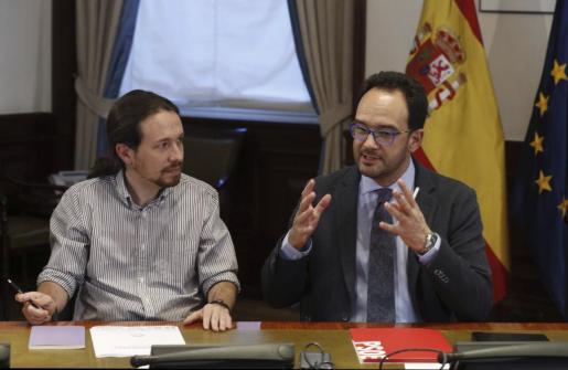 El líder de Podemos, Pablo Iglesias (i), y el portavoz del PSOE, Antonio Hernando, al inicio de la reunión entre PSOE, Podemos y Ciudadanos para explorar la posibilidad de negociar un acuerdo de gobierno, el pasado jueves en el Congreso.
