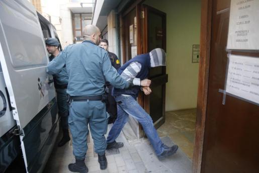 Agentes de la Guardia Civil trasladan a uno de los detenidos a los juzgados de Manacor.