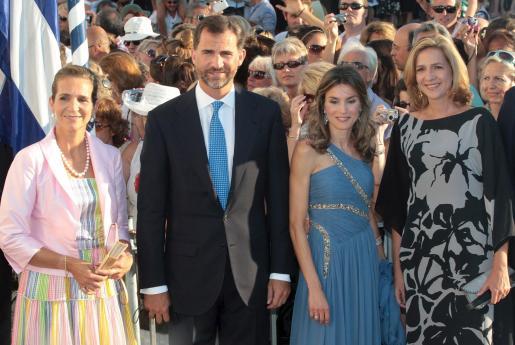 El príncipe Felipe, y su esposa, la princesa Letizia, (c-d), posan junto a la Infanta Elena, (i), y a la Infanta Cristina, (d), a su llegada al enlace matrimonial de Nicolás de Grecia con Tatiana Blatnik.