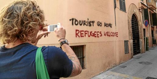 Un turista fotografía con su móvil una de las pintadas que han aparecido en el casco antiguo.