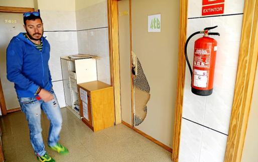 El jefe de estudios del Colegio de Educación Infantil y Primaria Joan Veny i Clar junto a una de las puertas que los ladrones rompieron a patadas.