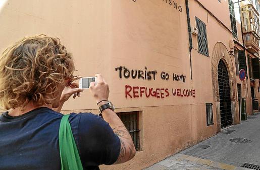 Un turista, fotografiando el miércoles una de las pintadas.