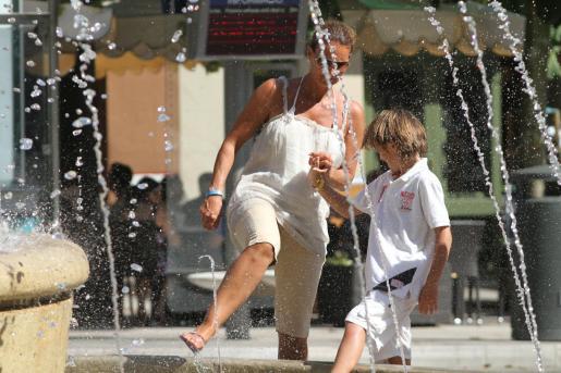 Algunos buscan huir del calor metiendo los pies en una fuente para refrescarse.