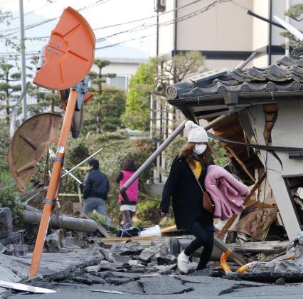 Los residente caminan entre los escombros de los edificios en Mashiki, en la prefectura de Kumamoto.