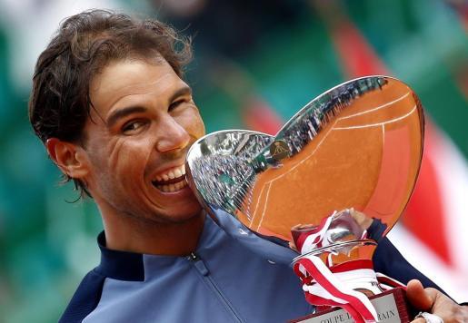 El español Rafael Nadal muerde el trofeo obtenido en Montecarlo.