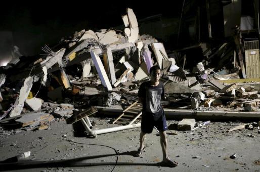 Un adolescente, ante un hotel reducido a escombros en Portoviejo.
