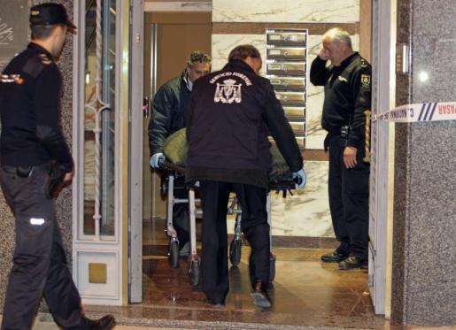 Efectivos de los servicios funerarios trasladan el cuerpo de la mujer de unos 30 años que ha aparecido muerta en una vivienda del sexto piso de un edificio sito en el Paseo de la Estación de Salamanca.