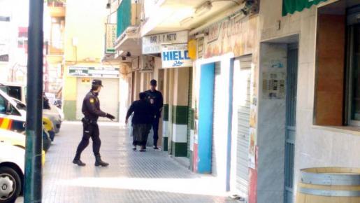 Agentes de la Policía Nacional hablan con una vecina, en el portal del edificio de viviendas donde vive el detenido.