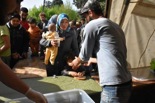 Adultos y niños hacen cola para recibir una bebida, un pedazo de pan y un huevo.