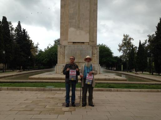 Dos miembros de CUP Palma posan ante el memorial de sa Feixina con el cartel de la campaña 'Els carrers de la vergonya '.