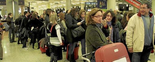 El Gobierno español decidió militarizar los aeropuertos, entre ellos los de Balears, tras el abandono masivo de sus puestos de trabajos por parte de los controladores aéreos. En la foto, un grupo de pasajeros hacen cola en Son Sant Joan.