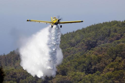 Foto de archivo de un avión transportando agua para sofocar las llamas.