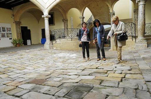 Desde la izquierda, Francisca Niell e Isabel Gomis explican a este diario que las piedras del patio del Casal Solleric han perdido consistencia porque se han ido abriendo en lajas y volatilizando.