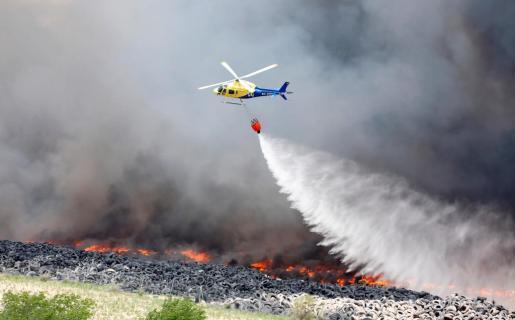 Un helicóptero descarga agua sobre el incendio declarado en un cementerio de neumáticos en la localidad de Seseña.