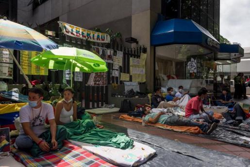 Fotografía de este martes, martes 31 de mayo de 2016, un grupo de personas que realizan una huelga de hambre desde hace más de 20 días para pedir la activación de la Carta Democrática Interamericana en la entrada del edificio donde se encuentran las oficinas de la Organización de los Estados Americanos (OEA) en Caracas (Venezuela).