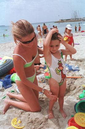 Una madre aplica a su hija la crema solar protectora en la playa de Can Pastilla.