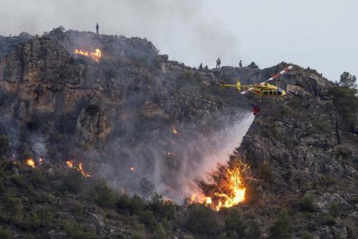 GRA458. CALASPARRA (MURCIA), 10/06/2106.- Doscientas personas trabajan esta noche en la extinción de un incendio declarado poco antes de las cinco de la tarde en la sierra del Molino y zona de los Albares de Calasparra, al que se incorporaron dos helicópteros de Castilla-La Mancha, otro de Muchamiel (Alicante), los autonómicos de Alcantarilla, Zarcilla de Ramos y La Pila, así como un avión de Torrejón (Madrid). EFE/Marcial Guillén Doscientas personas trabajan en extinción de un incendio en Calasparra