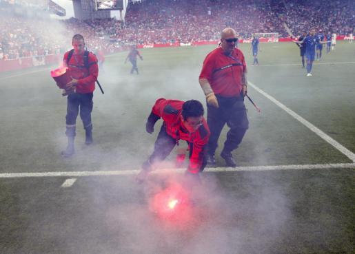 Operarios retiran bengalas lanzadas desde la grada en el estadio de Saint-Étienne durante el República Checa-Croacia.