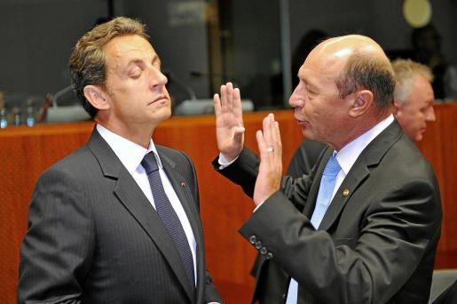 El presidente francés (i) conversa con su homólogo rumano, Traian Basescu, antes de comenzar la cumbre de líderes de la UE.