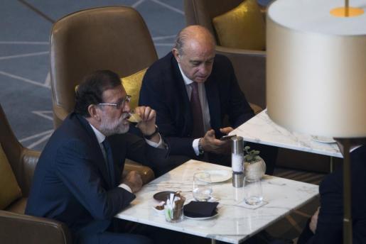 El presidente del Gobierno en funciones y líder del PP, Mariano Rajoy, acompañado por el ministro del Interior en funciones, Jorge Fernandez Díaz, poco antes de su intervención en un foro organizado en Barcelona por El Periódico de Catalunya.