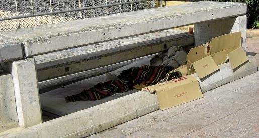 Imagen de la manta y los cartones de una de las personas que desde hace tiempo duerme bajo las gradas de la plaza de los Patines.