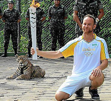 Brazilian physiotherapist Igor Simoes Andrade poses for picture next to jaguar Juma as he takes part in the Olympic Flame torch relay in Manaus, Brazil, June 20, 2016. Picture taken June 20, 2016. REUTERS/Marcio Melo FOR EDITORIAL USE ONLY. NO RESALES. NO ARCHIVES TPX IMAGES OF THE DAY