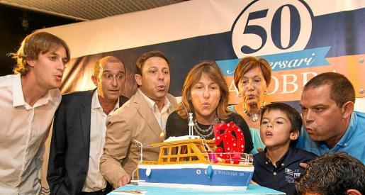 Momento en que la familia de Barcos Azules sopló las velas para conmemorar el 50 aniversario del 'Calobra' en una tarta réplica de la embarcación.