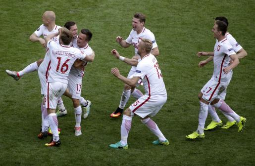Los futbolistas polacos celebran con alegría su clasificación para cuartos de final de la Eurocopa de Francia.