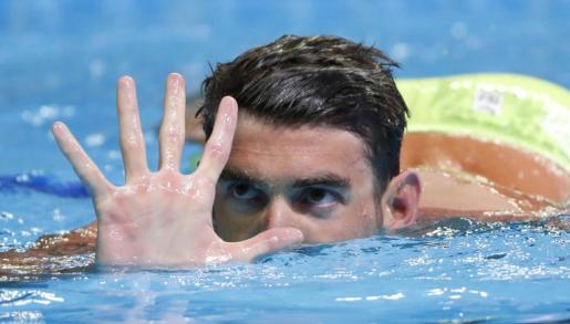 Michael Phelps indica con su mano su quinta participación en unos Juegos Olímpicos.
