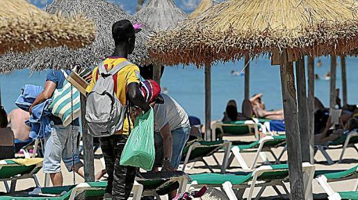 Un vendedor ambulante pasea por la playa de Palma.