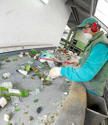 Un trabajador selecciona vidrios en la planta de selección de Tirme que después se reciclarán en la Península.