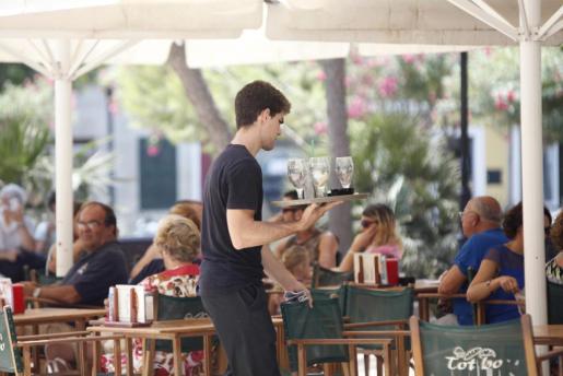 Un joven camarero trabajando en Ciutadella.
